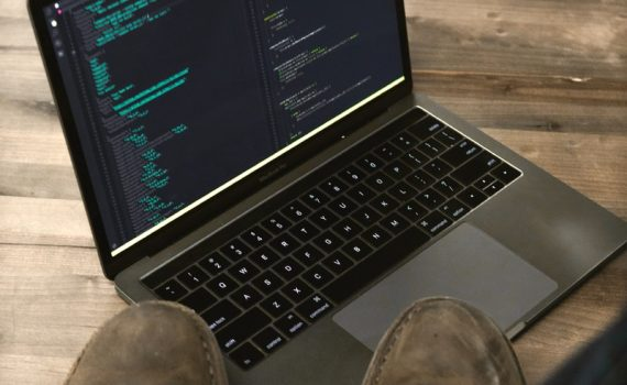 person's feet on table with turned-on laptop